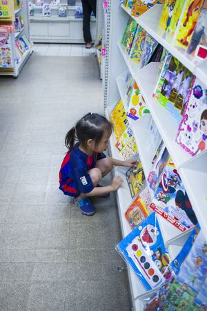 CHIANGMAI,THAILAND-MAY 3,2019 : Little Child explores the bookshelves  in book store High resolution image gallery.