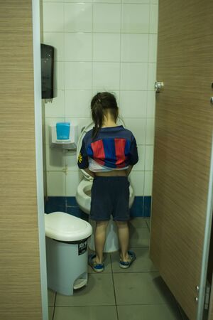 CHIANGMAI,THAILAND-MAY 3,2019 :   Long hair boy pee in toilet High resolution image gallery. Editorial