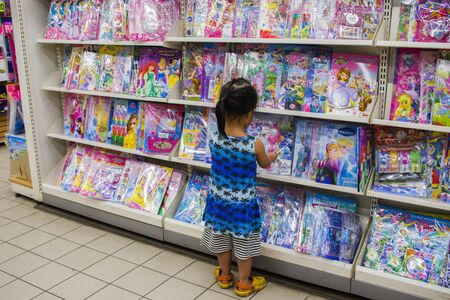 CHIANG MAI,THAILAND-MAY 3,2019 : Little Child explores the bookshelves  in book store High resolution image gallery. Editorial