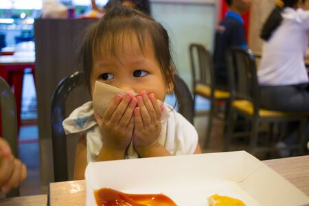 CHIANG MAI,THAILAND-MAY 3,2019 : Little Child eating fried chicken in the background of KFC restaurant. Editorial