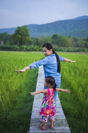 Happy Mother and her child play outdoors having fun, Green  rice field back ground. High resolution image gallery.