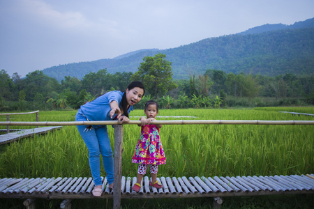 Happy Mother and her child play outdoors having fun in Green  rice field back ground. High resolution image gallery.