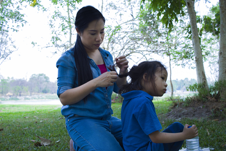 Happy asian mother ties  hair of her sun while the adorable male kid eating snacks. High resolution image gallery.
