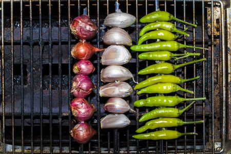 Garlic Shallot and fresh chili peppers roasting over a charcoal fire grill. prepare for cooking Thai food. High resolution image gallery.