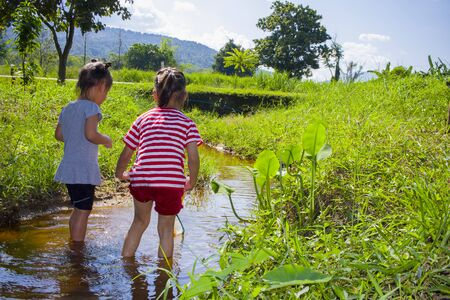 Asiatische Kinder spielen barfuß im Bachwasser, fangen einen Fisch, spielen Schlamm und Sand. Standard-Bild