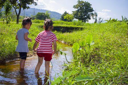 Los niños asiáticos que juegan descalzos en el agua de un arroyo, atrapan un pez juegan barro y arena. Foto de archivo