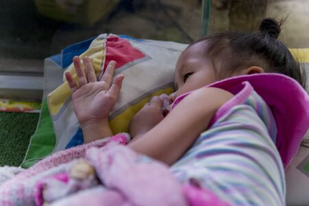 Sleeping Asian little cute baby sucking thumb