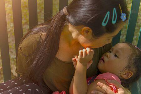 Joven madre abrazando y calmando a una pequeña hija llorando, madre asiática tratando de consolar y calmar a su niño llorando