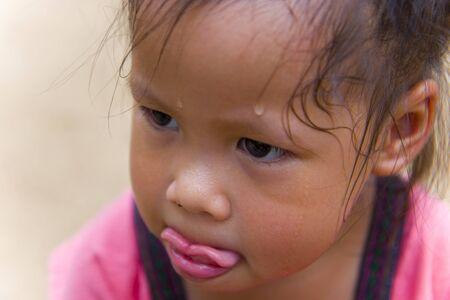 Cara de niño pequeño buscando algo y sudorosa en su cara Foto de archivo