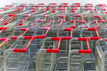 Parking trolleys with red handles at the supermarket environment.  High resolution image gallery. Banco de Imagens