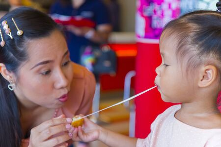 Mom and little child eating sticky stretch fried cheese ball together . feeling enjoyment.  High resolution image gallery.