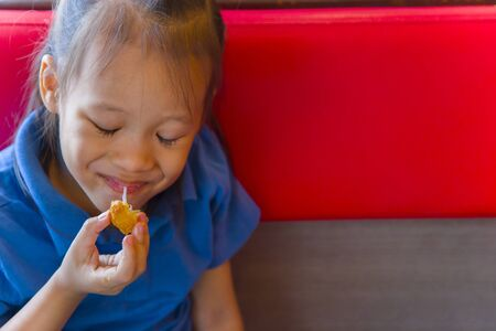 Little child asian eating sticky stretch fried cheese ball. feeling enjoyment.  High resolution image gallery.
