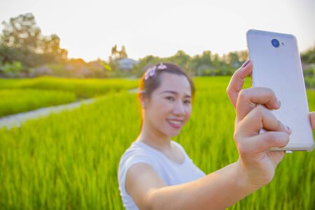 young happy and attractive Asian woman taking selfie portrait with internet mobile phone enjoying holidays of the sunset on the farmer's balcony in the rice fields  High resolution image gallery.
