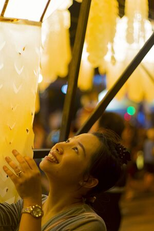 Portrait of Asian woman holding a traditional paper lantern during Yi peng (or Yee peng) festival in Thapae Gate Chiangmai
