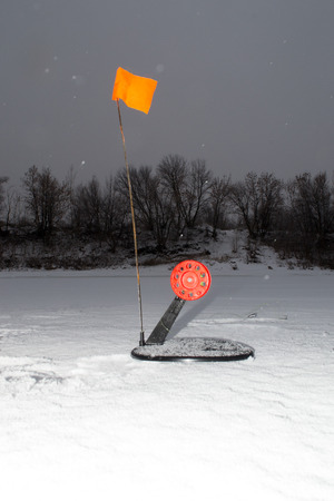 Winter imitation fish for predatory fish. The imitation fish is round with a red flag on the ice.