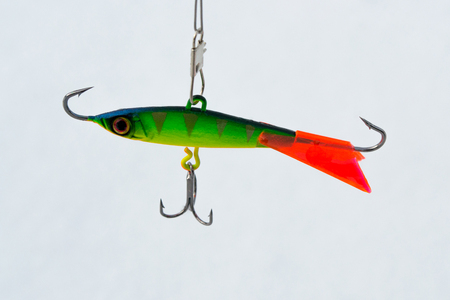 Winter bait balancer for predatory fish. Green balancer. With red fin and pattern. On a white snow background.