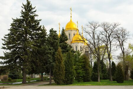 Beautiful Orthodox Church, play of light on the gilded dome, sky in the background. Dome of the church on the background of trees and sky. Dome of the church with a golden cross on the background of trees. Stockfoto