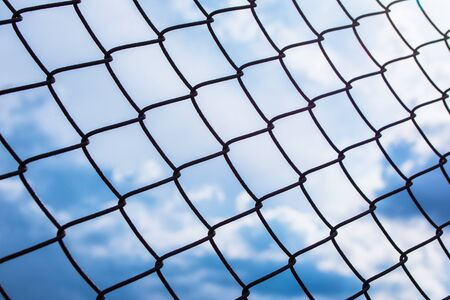 Metal black fence-mesh netting. Blue and white clouds on blue sky. The background image of the fence. Selective focus.