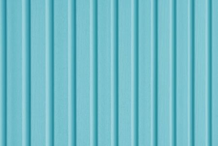 Element of the facade. Part of the facade decoration close-up. Facing material of buildings. Metal sheet roof. Vertical sheet. Blue color.