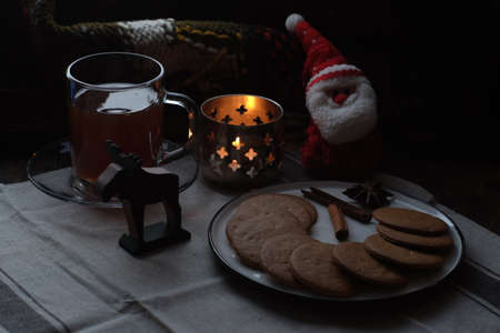 Christmas breakfast. Tea and gingerbread cookies plate, candle and soft toy Santa