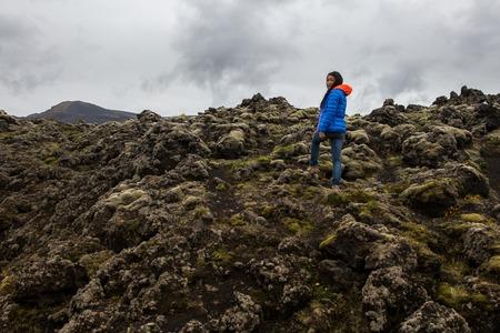 A woman stands on a moss overgrown lava field