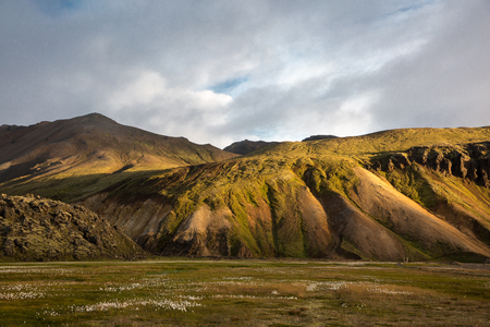 The suns rays make their way through the clouds against the backdrop of mountains and sunset in Iceland 写真素材