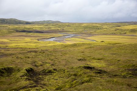 Endless lava fields covered with green moss crosses a small river, fancifully curving. Picture taken in Iceland