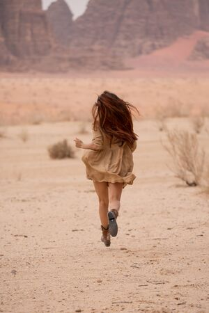model girl in boots and a short dress runs through the desert. Her long hair is developing. Back view. In the background a desert landscape