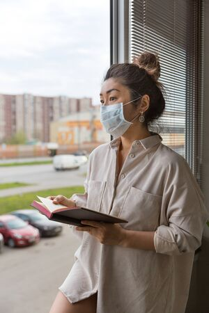 A girl in a medical mask and a man s shirt on his naked body stands at the window with a book. Standard-Bild