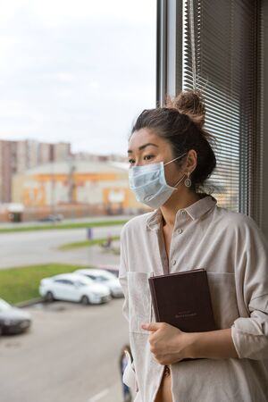A girl of Asian appearance in a medical mask and a man s shirt stands at the window with a diary in his hands. Standard-Bild