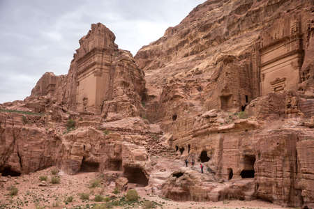A group of tourists climbs the stones of the ruined city of Petra