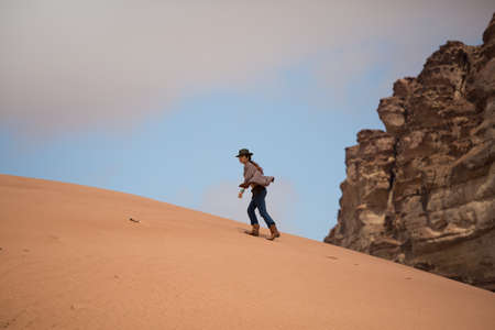 A girl in a shirt, a cowboy hat and boots walks along a sand dune, against a blue sky