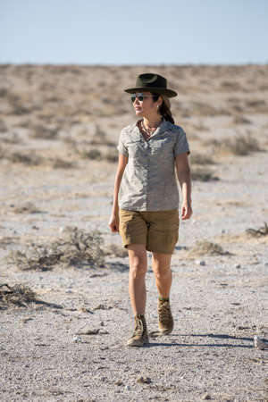 Namibia, Africa, June 18, 2019: Girl tourist in shorts and cowboy hat walks through the white desert