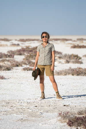 Namibia, Africa, June 18, 2019: Young beautiful girl tourist in shorts with a cowboy hat stands in the middle of the white desert