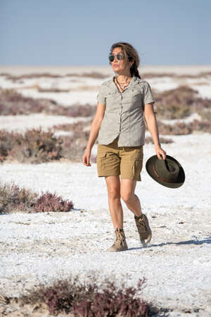 Namibia, Africa, June 18, 2019: A young beautiful girl tourist in shorts with a cowboy hat in her hand and sunglasses walks across the white desert