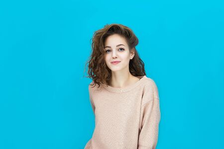 Portrait of a young beautiful woman wearing sweatshirt looking at you coquettishly isolated over blue background