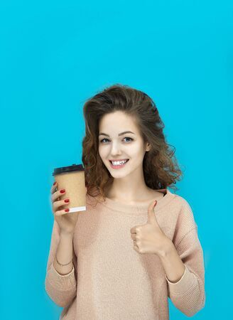 Portrait of a young beautiful woman wearing sweatshirt holding a cup with hot drink in hand and shows thumb looking at you over blue background Фото со стока