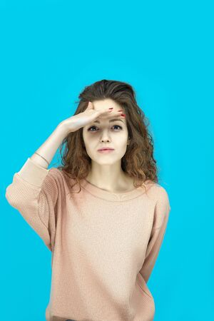 Portrait of a young beautiful woman wearing sweatshirt makes a visor with palm over the eyes and looking at you coquettishly isolated over blue background