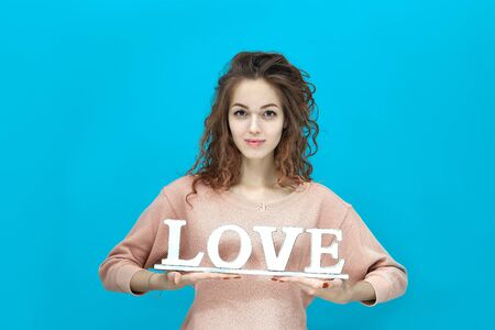 Portrait of a young beautiful woman wearing sweatshirt standing right holds the inscription love and looking at you coquettishly isolated over blue background