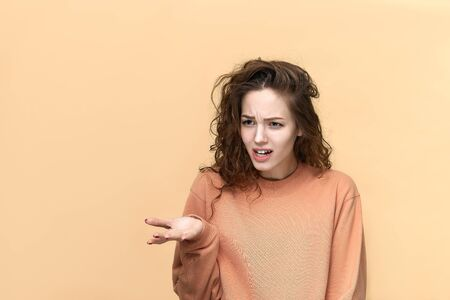 Portrait of a young beautiful woman wearing sweatshirt posing isolated over yellow background