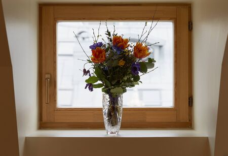 Bouquet of flowers in a vase on the window Фото со стока