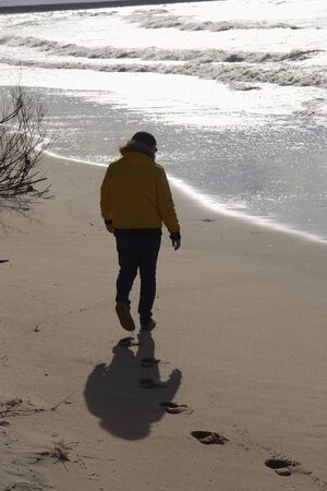 A man in a yellow winter jacket walks along the coastline leaving footprints in the sand