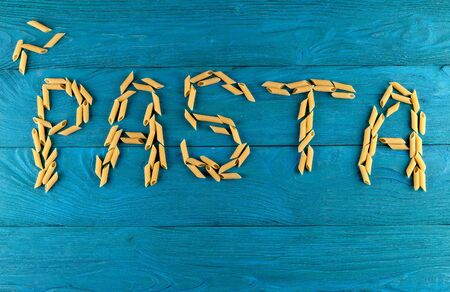 Word pasta laid out of raw pasta penne on blue wooden background