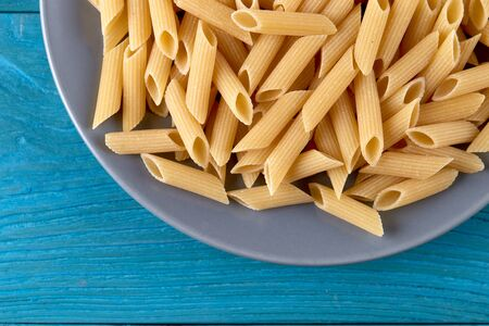 A lot of raw pasta penne on a plate at blue wooden background horizontal