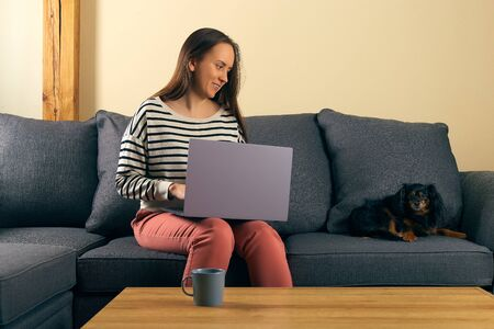 woman at remote work sitting on a sofa typing on a laptop smile and watching to her little dog