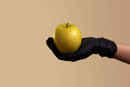 female hand in black latex glove holds a yellow apple over beige background