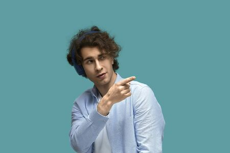 Talking to his. Portrait of a young beautiful man wearing white t-shirt and blue shirt in headphones point to something or somebody by his forefinger over blue background