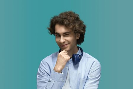 Blink. Portrait of a young beautiful man wearing white t-shirt and blue shirt in blue headphones.Thought and holds a fist at the chin and wink at camera over blue background Stock fotó