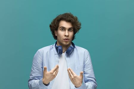 i did not do it. Portrait of a young beautiful man wearing white t-shirt and blue shirt in blue headphones points himself by palms and looking at the camera over blue background
