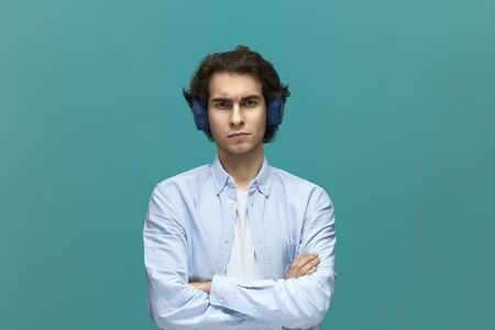 I will not do it. Portrait of a young beautiful man wearing white t-shirt and blue shirt with headphones fold ones arms and looking at camera over blue background.